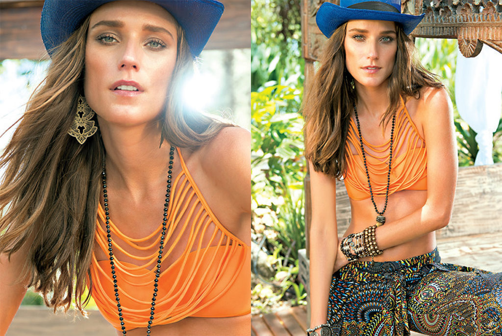 Model headshot posing with blue hat and orange top